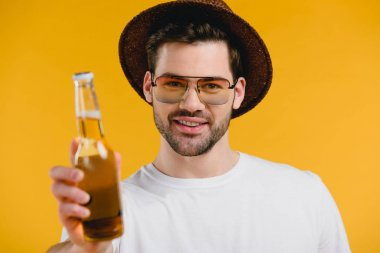 handsome young man in hat and sunglasses holding bottle with summer drink and smiling at camera isolated on yellow
