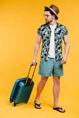 Handsome young man in summer outfit holding suitcase and looking away isolated on yellow stock vector