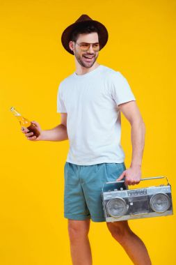 smiling young man in hat and sunglasses holding tape recorder and bottle of summer drink isolated on yellow