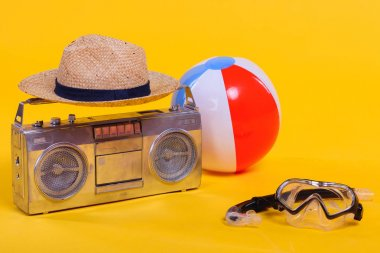 Tape recorder, hat, beach ball and snorkel with scuba mask isolated on yellow stock vector