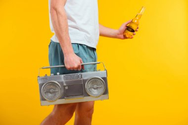 cropped shot of man in shorts holding tape recorder and glass bottle of summer drink