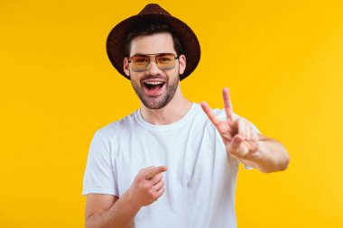 cheerful young man in white t-shirt, hat and sunglasses showing victory sign and pointing with finger isolated on yellow