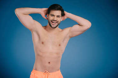Handsome shirtless young man standing with hands behind head and smiling at camera on blue stock vector