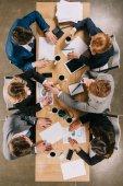 Pohled shora podnikatelé diskusi u stolu s digitálními zařízeními, šálky s kávou a dokumenty