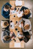 Fotografie pohled z obchodníků s digitálními zařízeními, šálky s kávou a dokumenty o u stolu