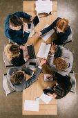 Pohled shora podnikatelé pracující u stolu s dokumenty, notebooku, tabletu a smartphonu
