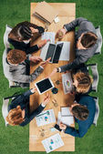 Top view of business colleagues working at table with laptop, smartphone and tablet in office
