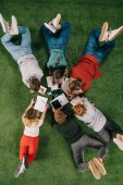 Fotografie Top view of laying business colleagues working with documents and devices on grass
