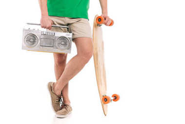 cropped shot of young man in shorts holding skateboard and tape recorder isolated on white