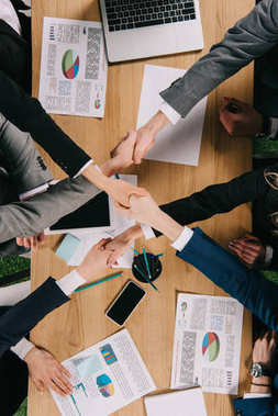Cropped view of business partners shaking hands at table in office