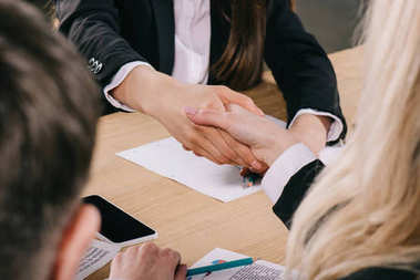Cropped view of two businesswomen shaking hands at table in office