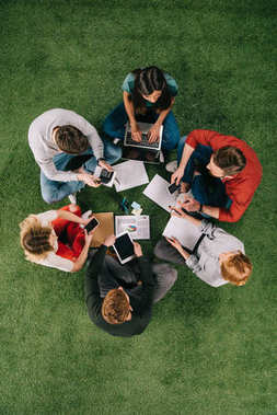 overhead view of businesspeople working with devices and documents on grass