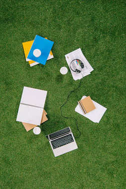 Heap of business objects and office supplies laying on green grass carpet