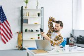 Fotografie Freier Mitarbeiter arbeiten von Laptop und Smartphone in hellen Büro halten