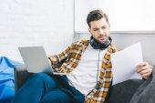 Fotografie Geschäftsmann durchlöchern Papier Büro auf Sofa zu Hause sitzen und laptop