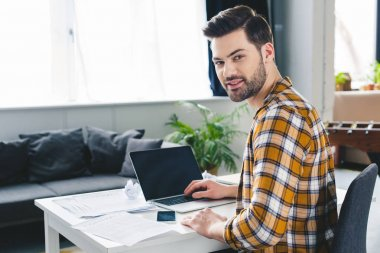 Young businessman working by laptop in light office