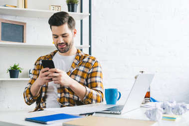 Young freelancer working by table and using smartphone at home office