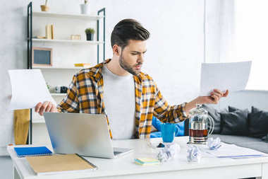 Man working by laptop and holding papers in light office