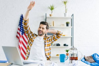 Smiling man stretching by working table at home office