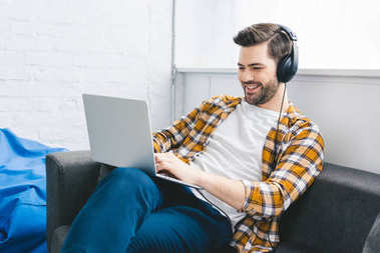 Man in headphones working on laptop in light office stock vector