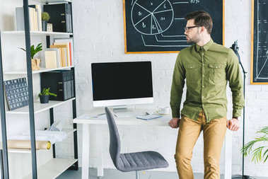 Businessman standing by table with computer at home office