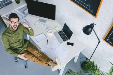 overhead view of excited man sitting by table with computers in light office