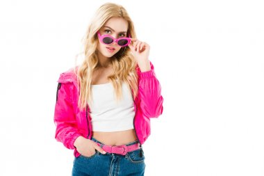 Attractive young woman dressed in pink touching sunglasses isolated on white