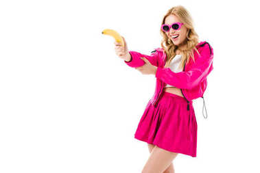 Attractive young woman dressed in pink shooting from banana isolated on white