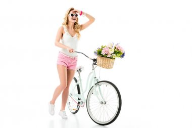 Blonde woman in sunglasses standing by bicycle with flowers in basket isolated on white stock vector