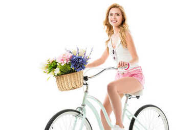 Attractive young woman riding bicycle with flowers in basket isolated on white stock vector