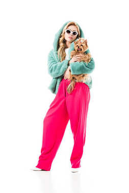 Blonde woman in fur coat holding cute Yorkie isolated on white