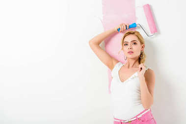 Blonde woman in pink clothes painting wall with roller