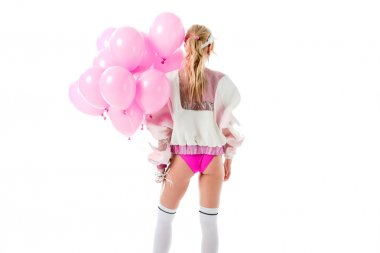 Attractive young woman dressed in pink holding pink balloons isolated on white