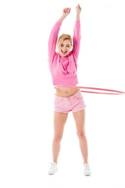 Blonde woman in pink clothes exercising with hula hoop isolated on white