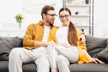 young smiling couple relaxing on comfy couch at home