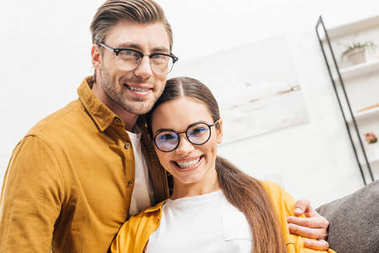 happy young couple embracing at home and looking at camera