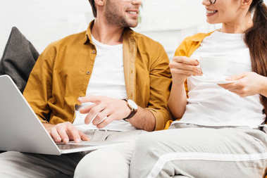 cropped shot of couple with coffee and laptop sitting on couch together