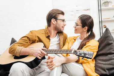 Handsome young man with guitar flirting with girlfriend at home stock vector