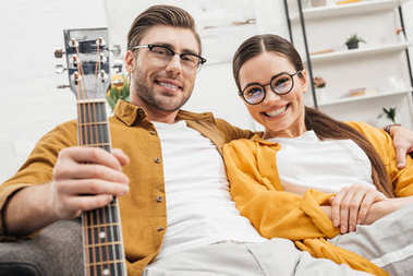 Happy relaxed couple with guitar sitting on couch at home stock vector