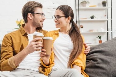 young happy couple flirting and clinking paper cups of coffee on couch