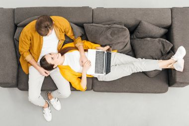 top view of happy woman lying on knees of boyfriend and working with laptop on cozy couch at home
