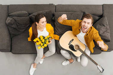 Overhead view of man with guitar raising fists and shouting while his girlfriend holding bouquet on couch at home stock vector