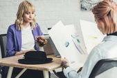 Photo selective focus of tattooed designer looking at sketches at workplace with colleague near by in office