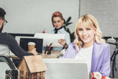 Photo selective focus of smiling blogger at workplace with colleagues behind in office
