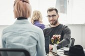Photo selective focus of smiling businessman in eyeglasses at workplace in office