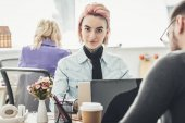 Photo selective focus of tattooed businesswoman at workplace with colleagues near by in office