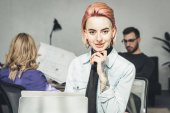 Photo selective focus of smiling tattooed businesswoman at workplace with colleagues near by in office