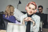 Photo selective focus of tattooed businesswoman in headphones at workplace in office