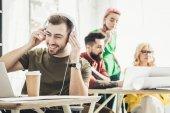 Fotografia messa a fuoco selettiva delluomo in cuffie con il caffè per andare e colleghi creativi che lavorano dietro in ufficio sorridente