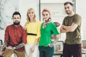 Photo portrait of group of young stylish creative workers looking at camera in office
